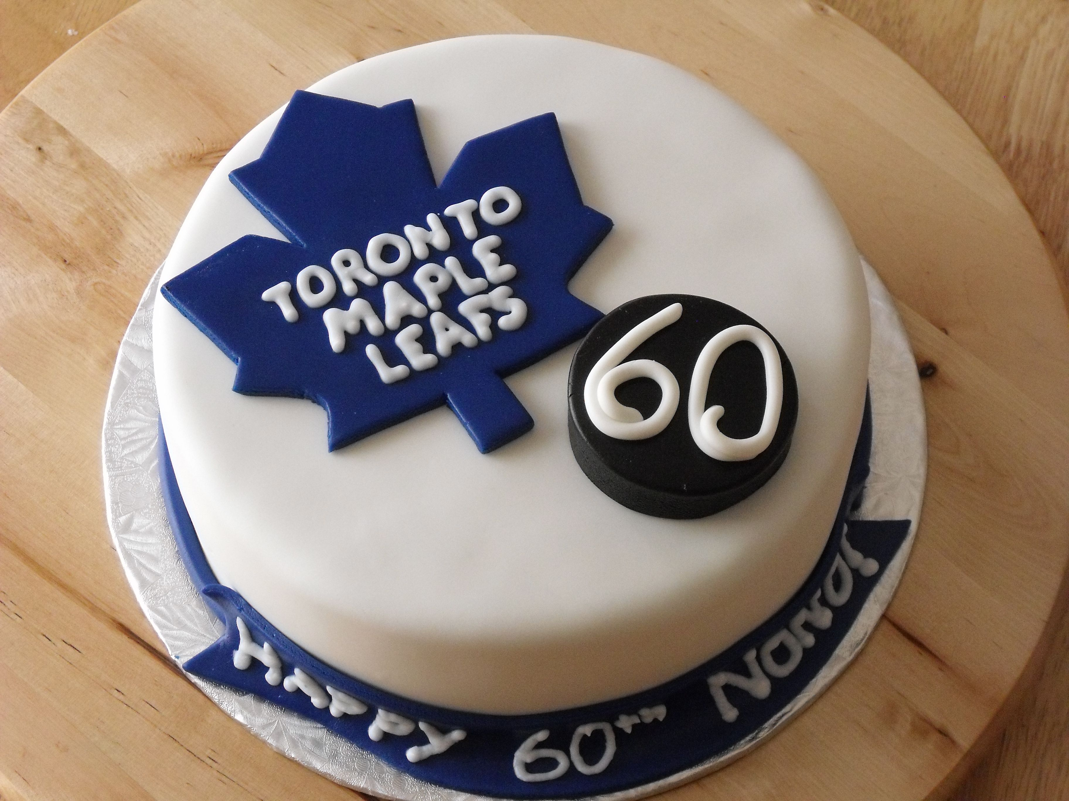 """Toronto Maple Leafs 60th - Customer requested a leafs theme cake for a big fan turning 60... this is what I came up with. Was planning a hockey puck cake but my black mmf would NOT work to cover a cake. I was happy with this result just the same. 8"""" vanilla butter cake w/ strawberry buttercream filling. All mmf, w/ roayl icing writing."""