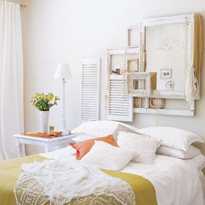 A gorgeous bright bedroom using frames and window panes as decor.