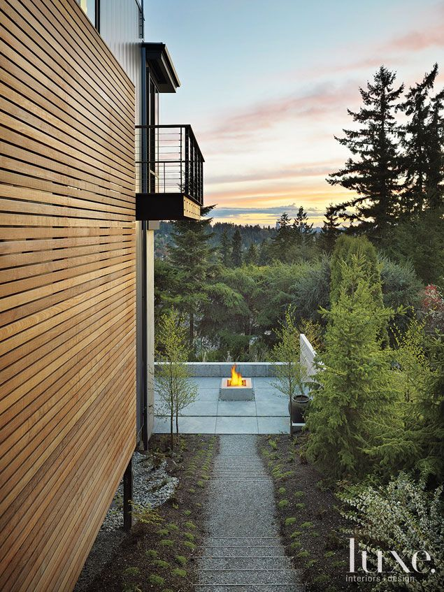 A pathway leads to a hillside terrace featuring a concrete fire pit