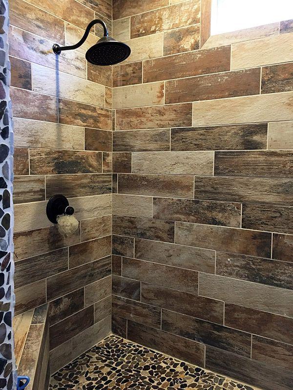 wood look tile shower with pebble floor  farmhouse shower