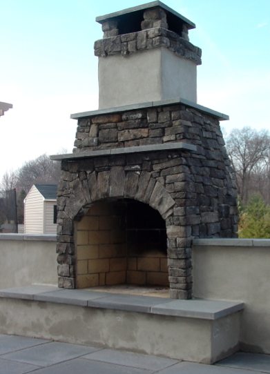 Outdoor fireplace made out of a Fire Rock kit.  Mortared cultured stone veneer with Bluestone mantel and accents.  Stucco walls and accents.