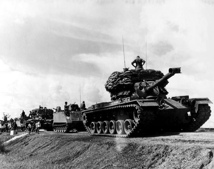 Tanks and ACAV's secure supply route in 25th Infantry Divison area. Sandbags modify vehicles for security role as movable pillboxes. (Vietnam War)