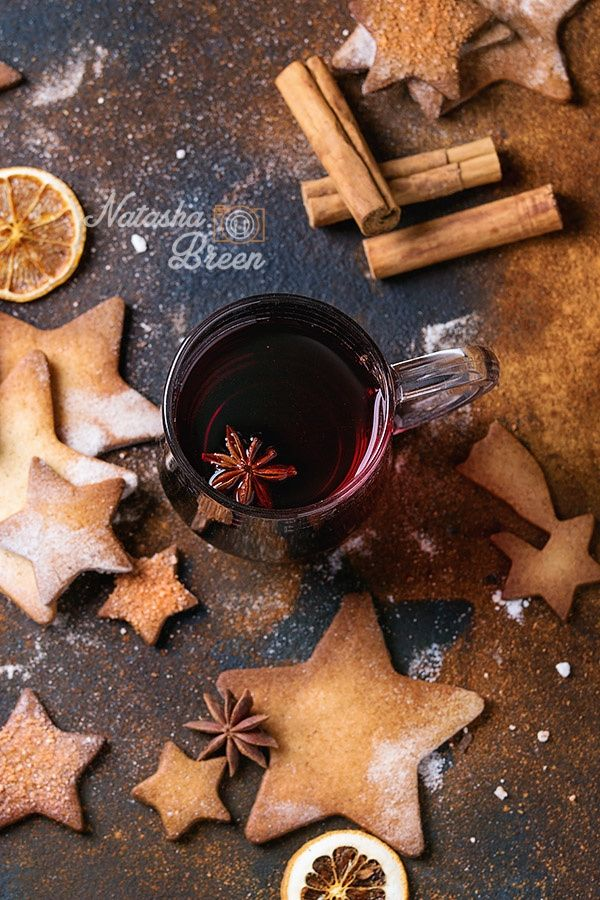 Mulled Wine with Cookies - Glass mug of hot red mulled wine spices, sugar shortbread cookies star shape, anise and cinnamon powder over dark textured background. Christmas drink treat theme. Overhead view