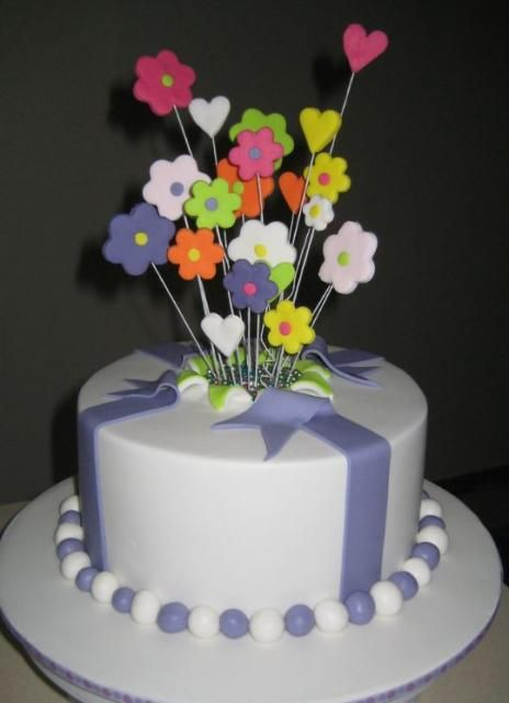 Round white cake with fondant flowers popping out of the middleJPG