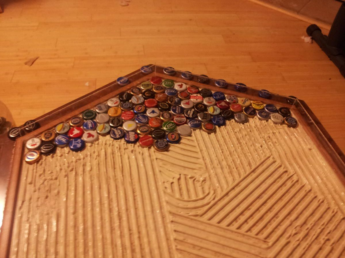Started laying the caps in the tile glue of the beer cap for How to make a table out of bottle caps