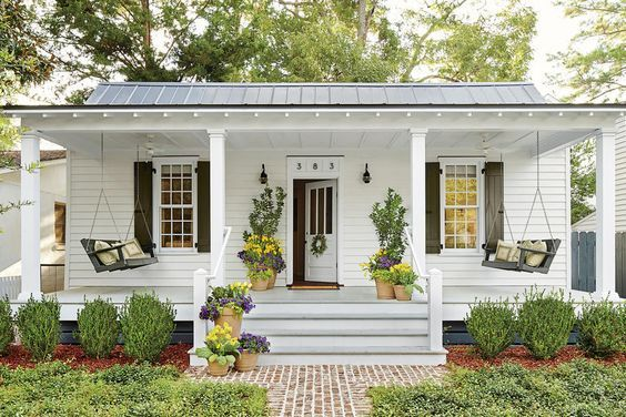 """Make Your Porch a Priority - 6 Tips for Living in a 660-Square-Foot Cottage  Southernliving. """"Always make room for porch conversations,"""" says Gibson. He widened and deepened the front stoop, turning it into a porch that's 28 by 8 feet. """"Lumber comes in 8-foot lengths, perfect for seating groups, and we didn't have an inch of waste,"""" he says. Rather than crowd the porch with furniture, they hung dueling porch swings and encourage guests to pull out chairs. Trim applied above the original…"""