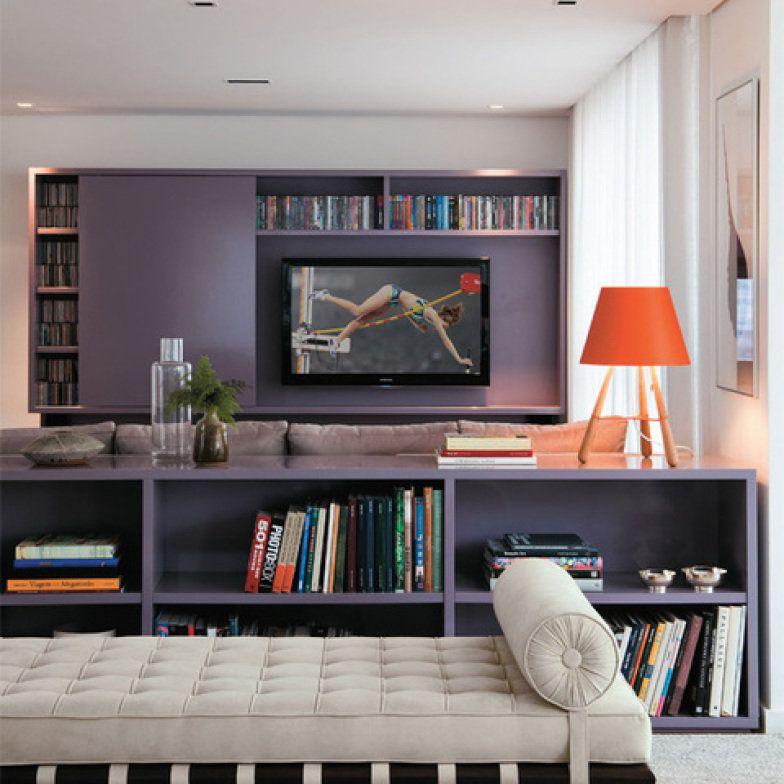 Com bastante espaço para armazenamento de livros, CDs e filmes, este home theater recebeu uma base clara e neutra que destacou o mobilário em tom roxo.