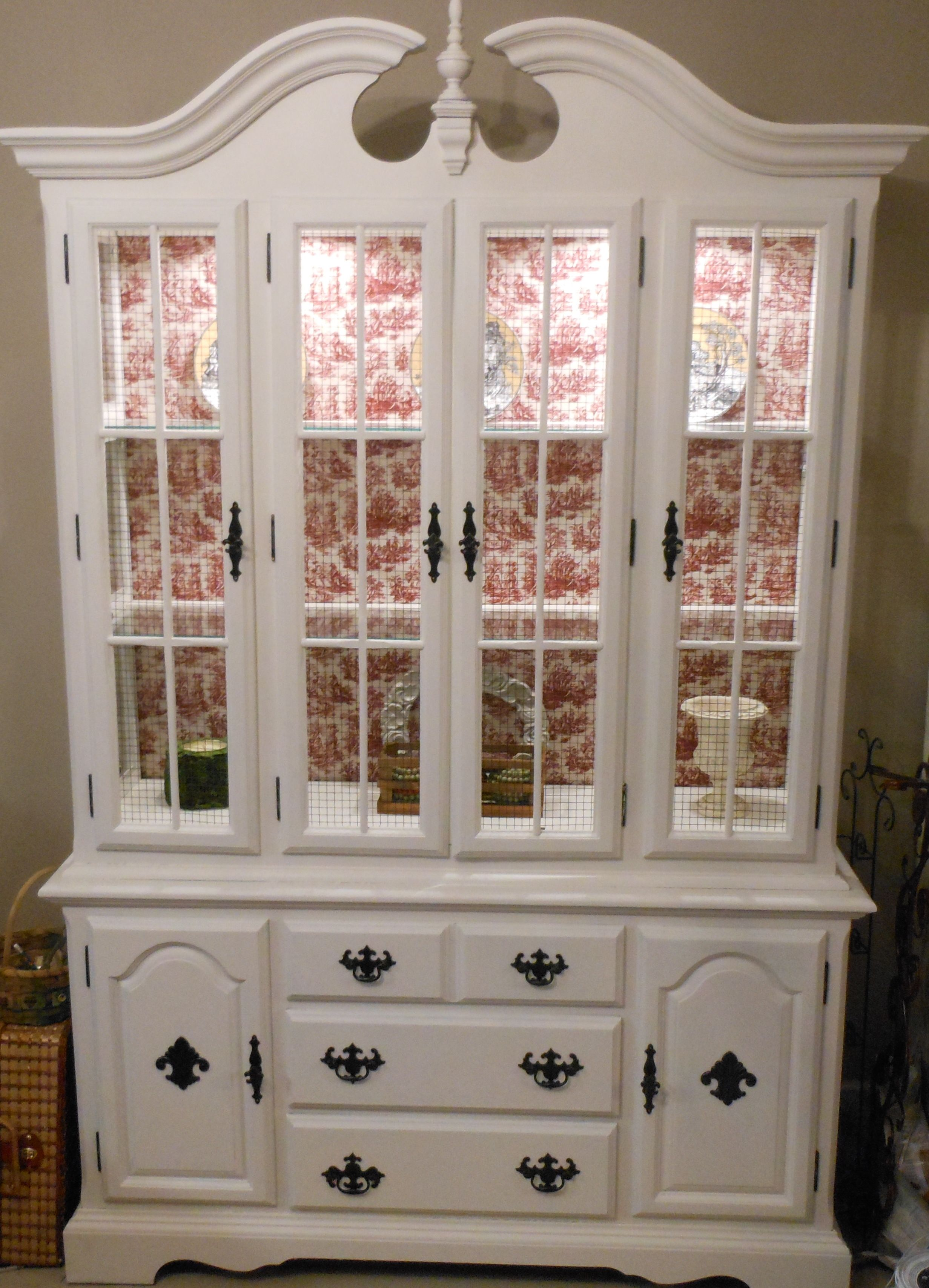 French Country hutch.  This was a dark cherry hutch when I found it.  I used Zinzer primer (don't need to sand the wood with this stuff).  I painted 2 coats of Antique White and spray painted the pulls and knobs black (found these Fluer De Lis knobs for all of the doors and appliques for the bottom doors at Hobby Lobby and spray painted them) and added chicken wire (primer and spray painted black) to the top doors. I also pulled the back panels off (which were initially mirrors) and wrapped…