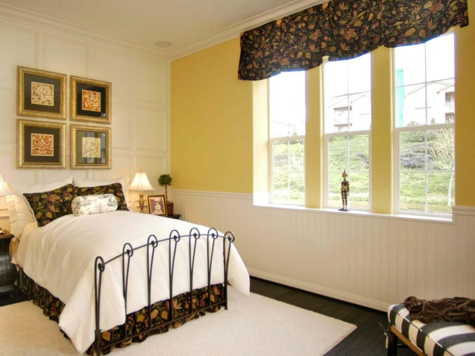 In the guest bedroom, traditional wainscoting forms a backdrop for ...