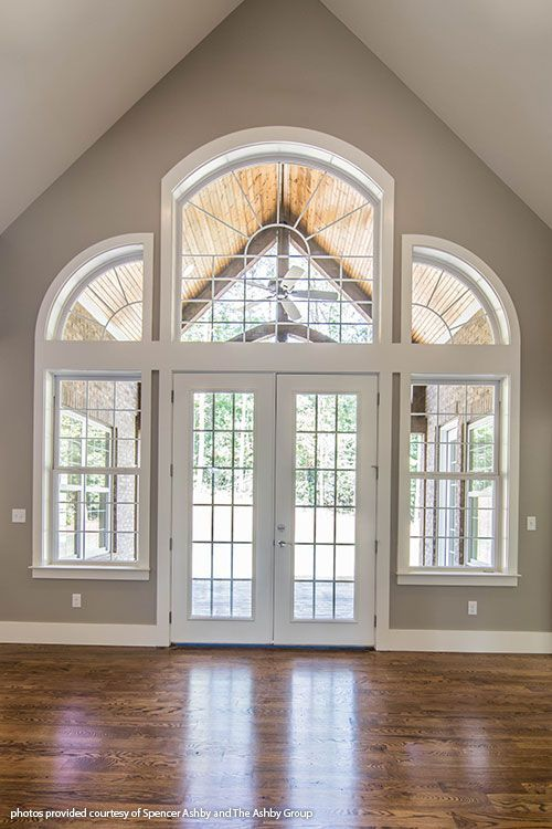 French doors are surrounded by floor-to-ceiling windows in this ...