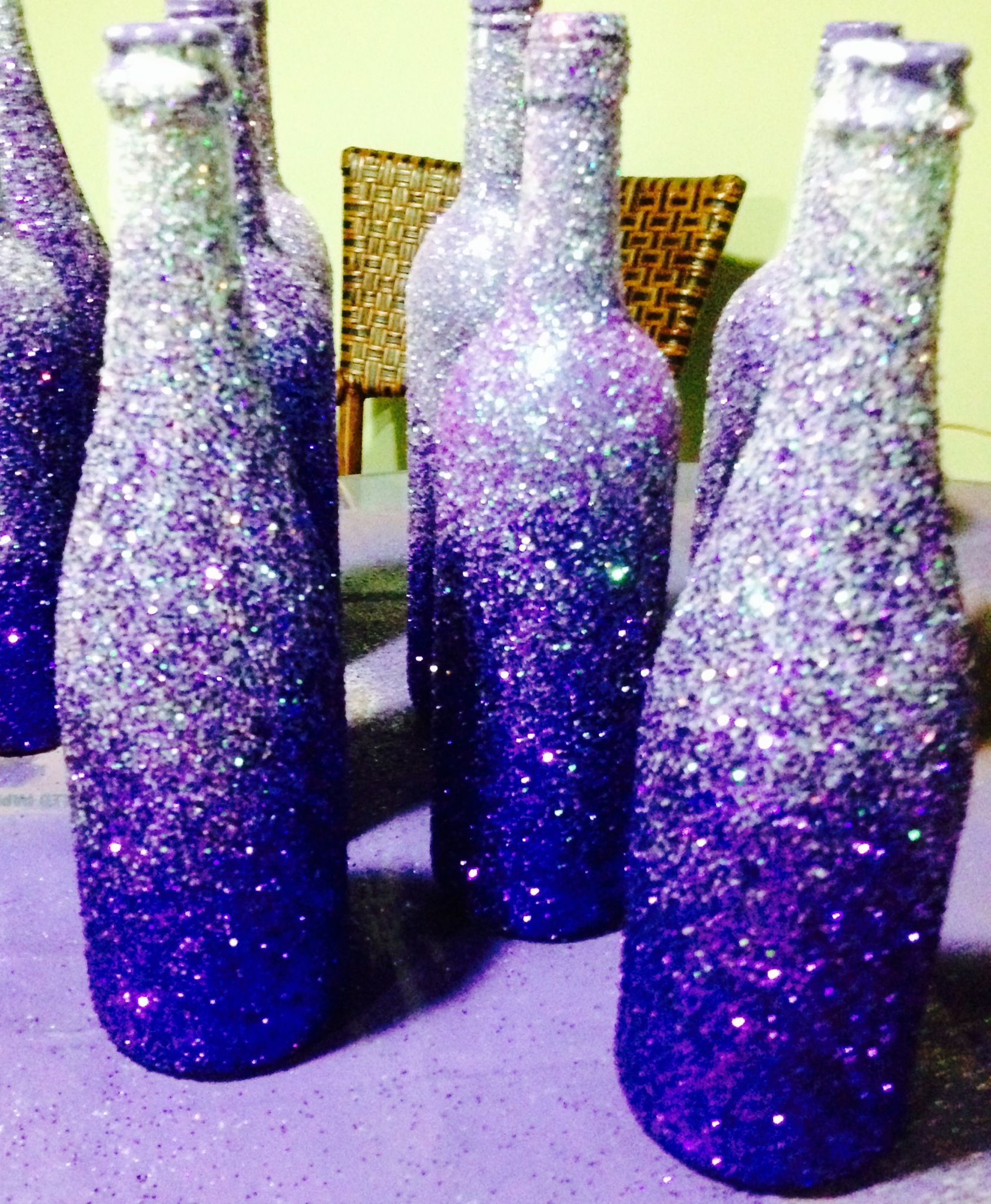 glittered wine bottles we spray painted the bottles with purple paint. Black Bedroom Furniture Sets. Home Design Ideas