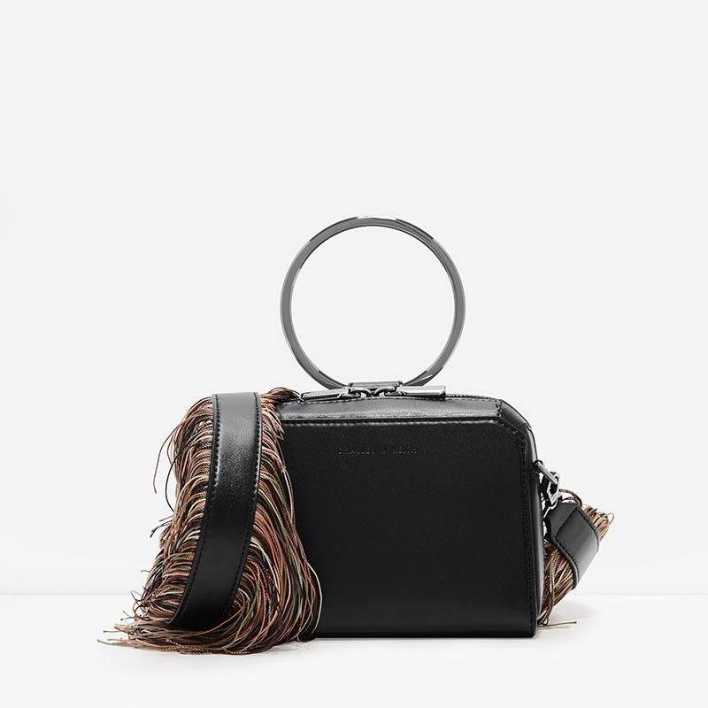 Black boxy crossbody bag featuring a metallic ring top handle and multi-coloured fringe strap.