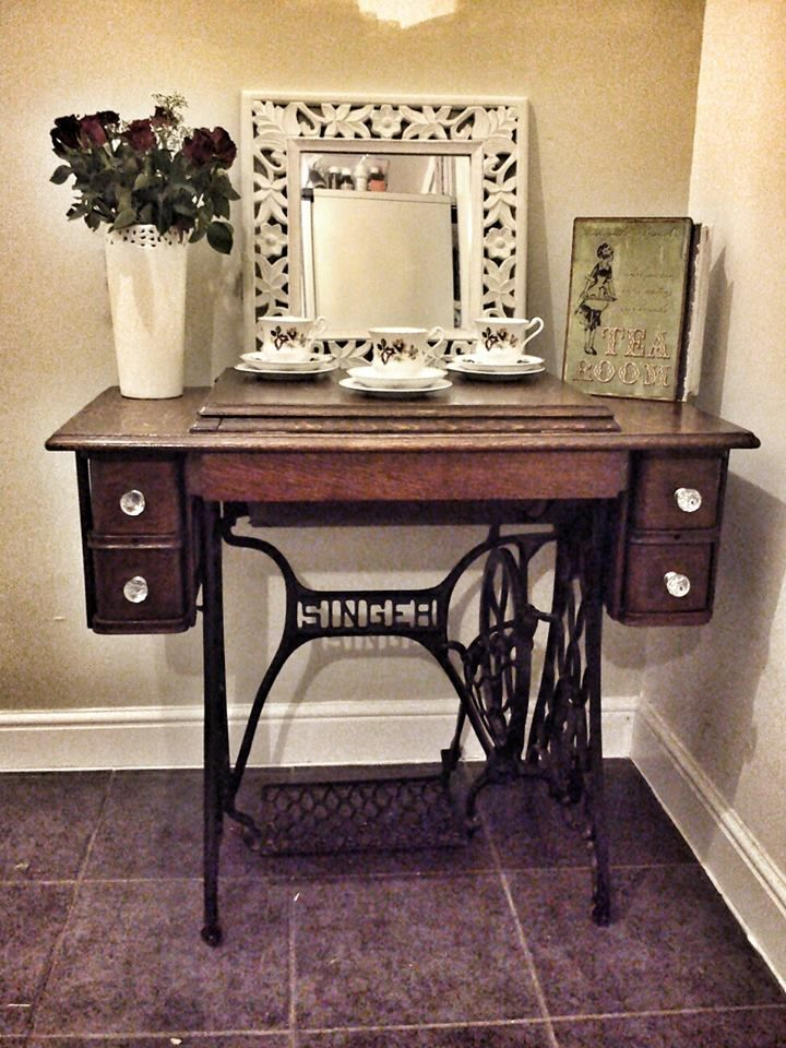 singer sewing machine table . Picture display, maybe? Like, ancestors' photos? :) (My great great grandmother had a singer sewing machine table like this, which we had in our house when I was growing up....I used to pump my foot on the pedal and pretend I was sewing, back when I was a little kid. lol.)