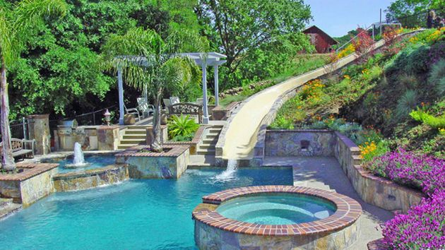 15 gorgeous swimming pool slides pool slides swimming for Garden swimming pool with slide