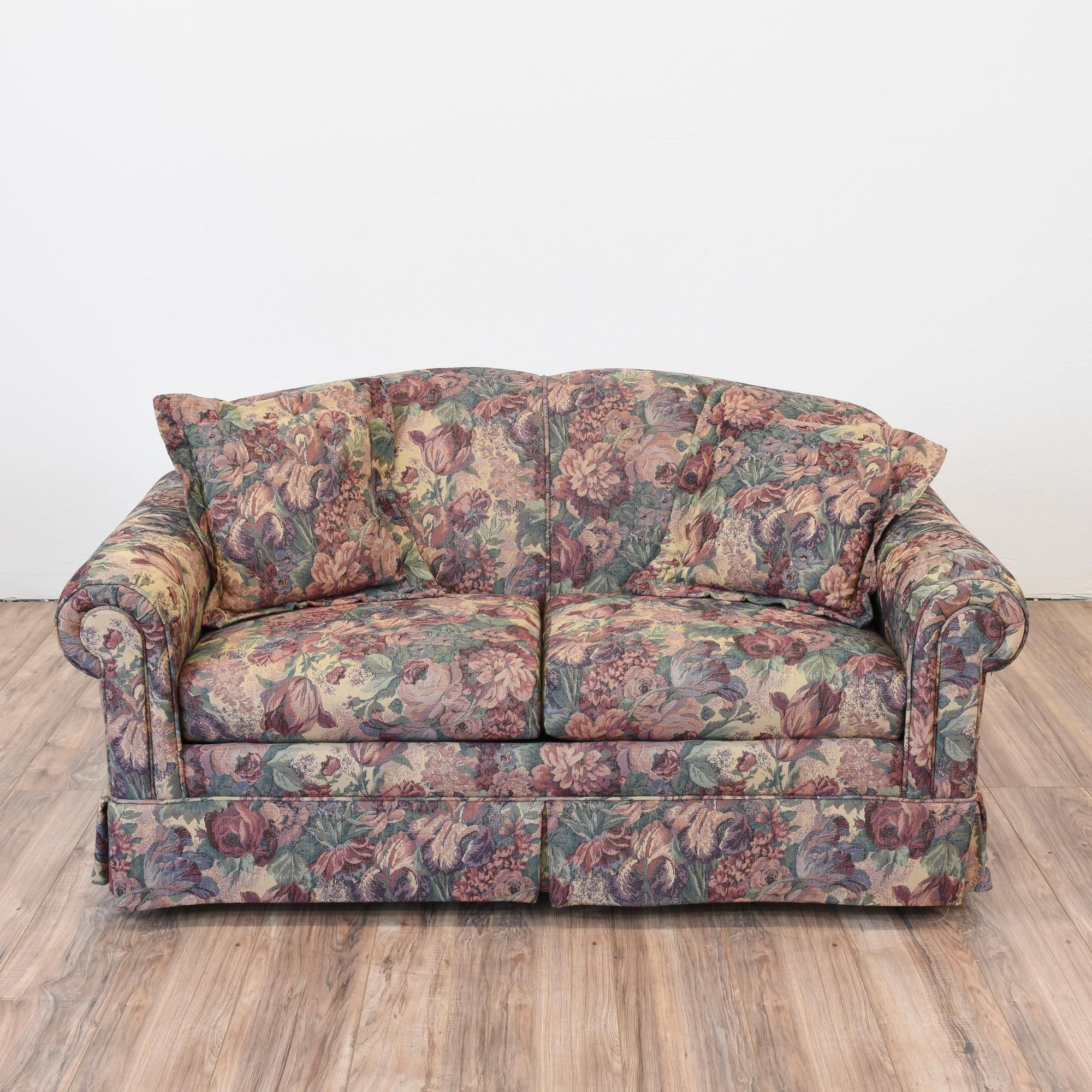 This loveseat is upholstered in a durable floral print fabric in a