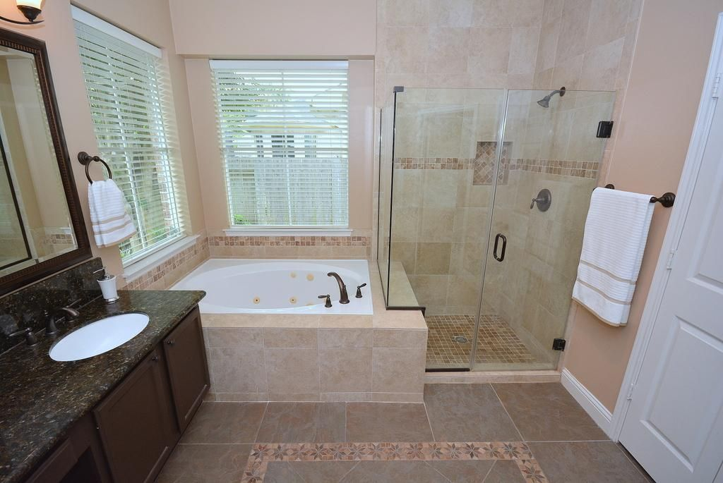 The bathroom also features a frameless shower door with ceramic ...