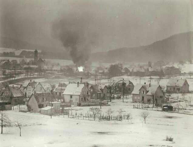 U.S. forces trying to recapture Wingen-sur-Moder from German mountain 6. SS-Gebirgsjäger Division troops, who infiltrated it during the night, dislodging American troops and taking a number of prisoners. Hotel 'Wenk' and Gasoline are in yard and hit by a tracer bullet, resulting in the burning, as seen in photograph. In the church tower on the left is a German lookout, who is also sniping at the U.S. soldiers.
