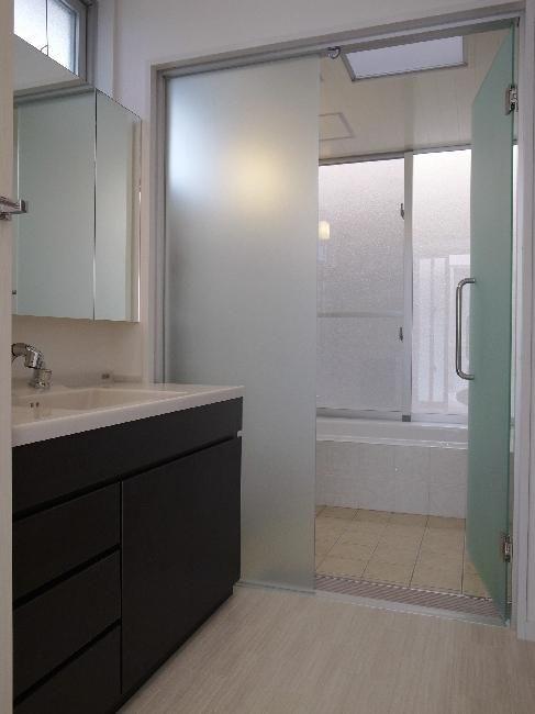 洗面室より浴室を見る A House 光を取り込む住まい バス トイレ事例 Suvaco スバコ シンプル バスルーム 浴室 ガラスドア 浴室 扉