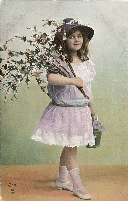 Girl in light purple dress, holding branches & pail