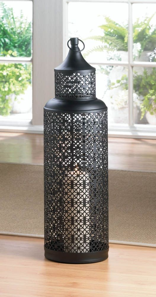 Simply stunning! This marvelous black iron lantern features an intricate cutout pattern that will turn the glow from your favorite candle into breathtaking ambiance. Hang it from the top loop or set it on your tabletop.
