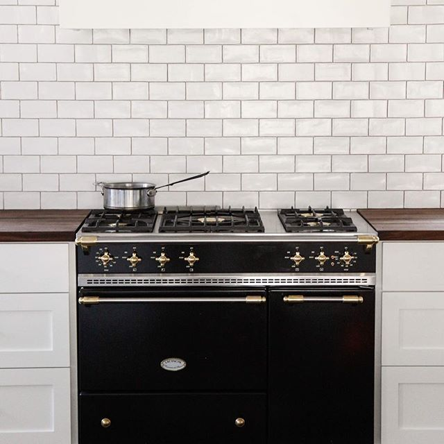 Delightful A Black French Stove Range Flanked By White Shaker Cabinets Topped With  Dark Butcher Block Countertops