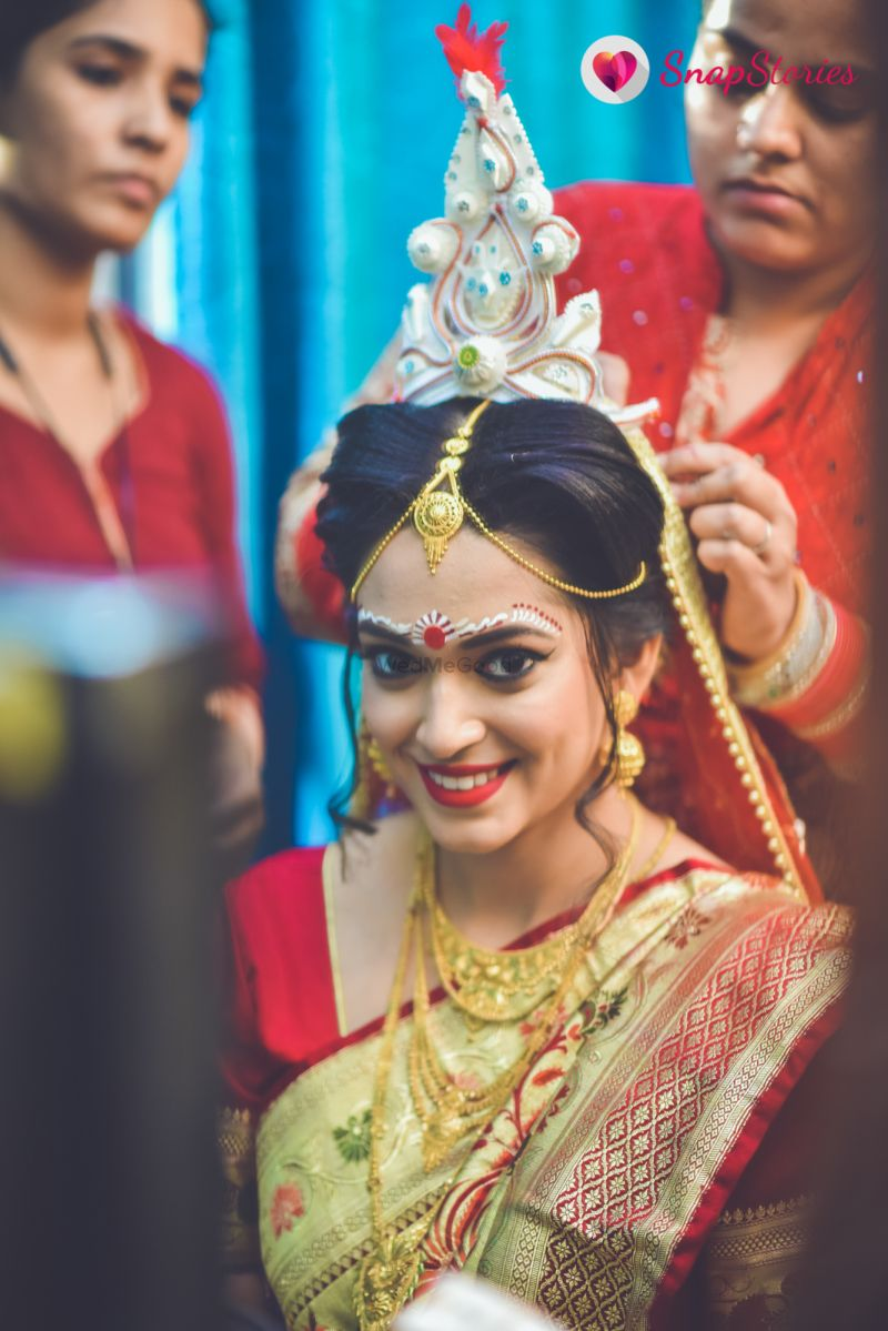 stunning bengali bride with traditional makeup and headgear