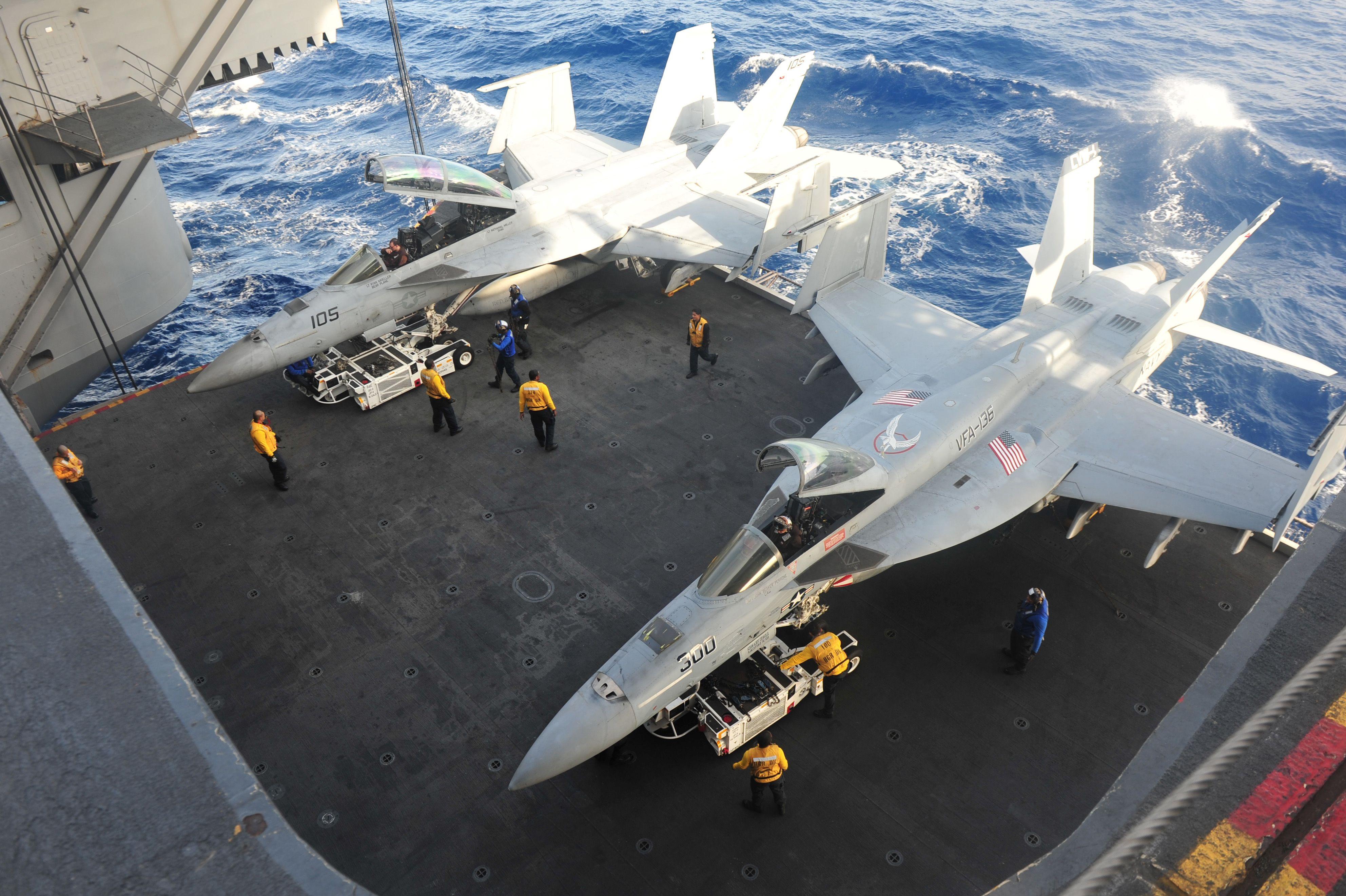 Sailors Lower Aircraft From The Flight Deck To The Hangar Bay On An Aircraft Elevator Aboard Tha Aircraft Carrier Uss Aircraft Carrier Fighter Jets Flight Deck