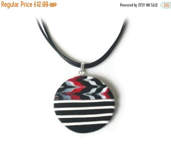 Black Pendant Necklace  SALE  Black White by Lottieoflondon  If your looking for a simple monochrome statement this season this Black Pendant Necklace is perfect, handmade from polymer clay in black featuring a feathered print with a bold white stripes and strung onto a double black leather thong. #jewelry #jewellery #necklace #pendant #black #white #blackpendant #blackwhitenecklace #blacknecklace #monochrome #whattowear #fashion #mystyle #giftideas #etsy