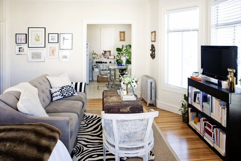 grey black white with zebra rug and faux fur brown throw, vintage cane back chair in white, scrunched together gallery wall with black white frame