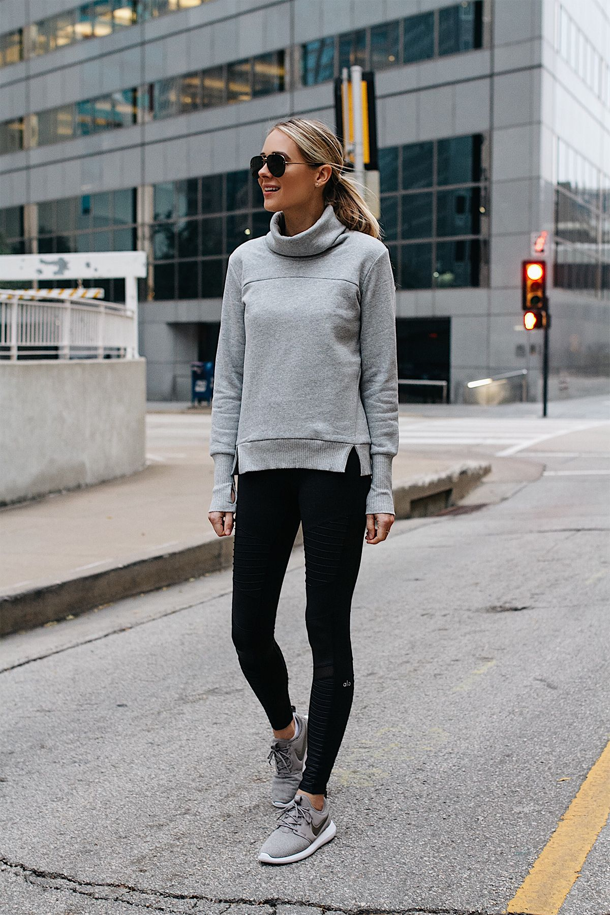 Blonde Woman Wearing Alo Grey Funnel Neck Sweatshirt Alo Black Moto  Leggings Nike Roshe Two Knit