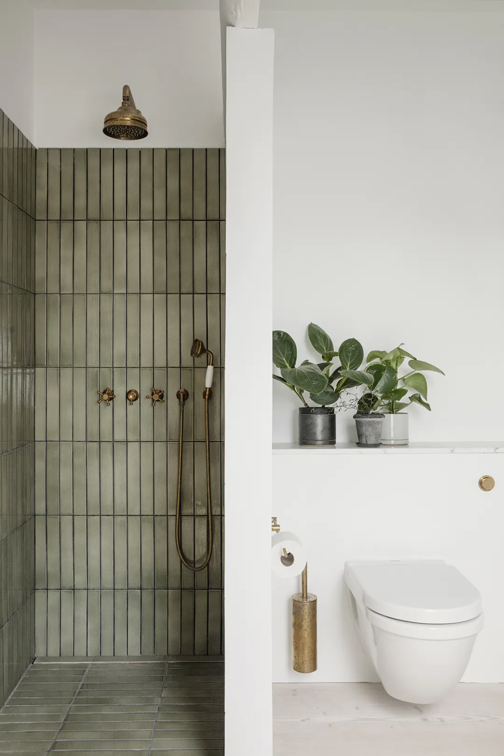 Bathroom in a nordic style with dark green tiles.