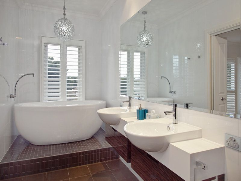 Ensuite Bathroom Lighting plantation shutters on ensuite window behind bath. light fitting