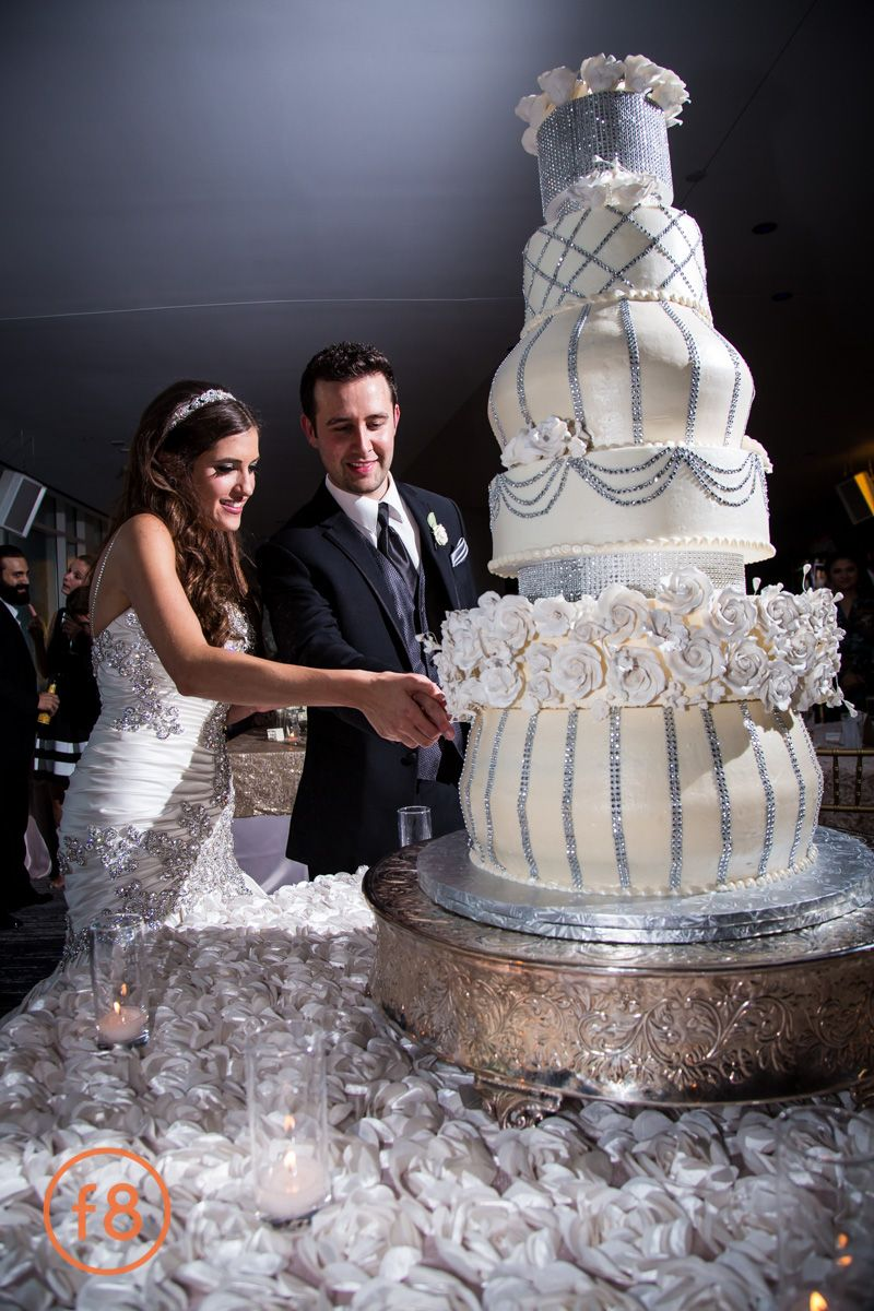 Absolutely beautiful six tier fantasy wedding cake. Crystals and creams on a silver wedding cake stand. Beautiful ruffled floral linen. It's like a dream out of Aladdin. Pnina Tornai wedding dress. W Hotel Dallas, TX. Dallas wedding photography. f8studio.