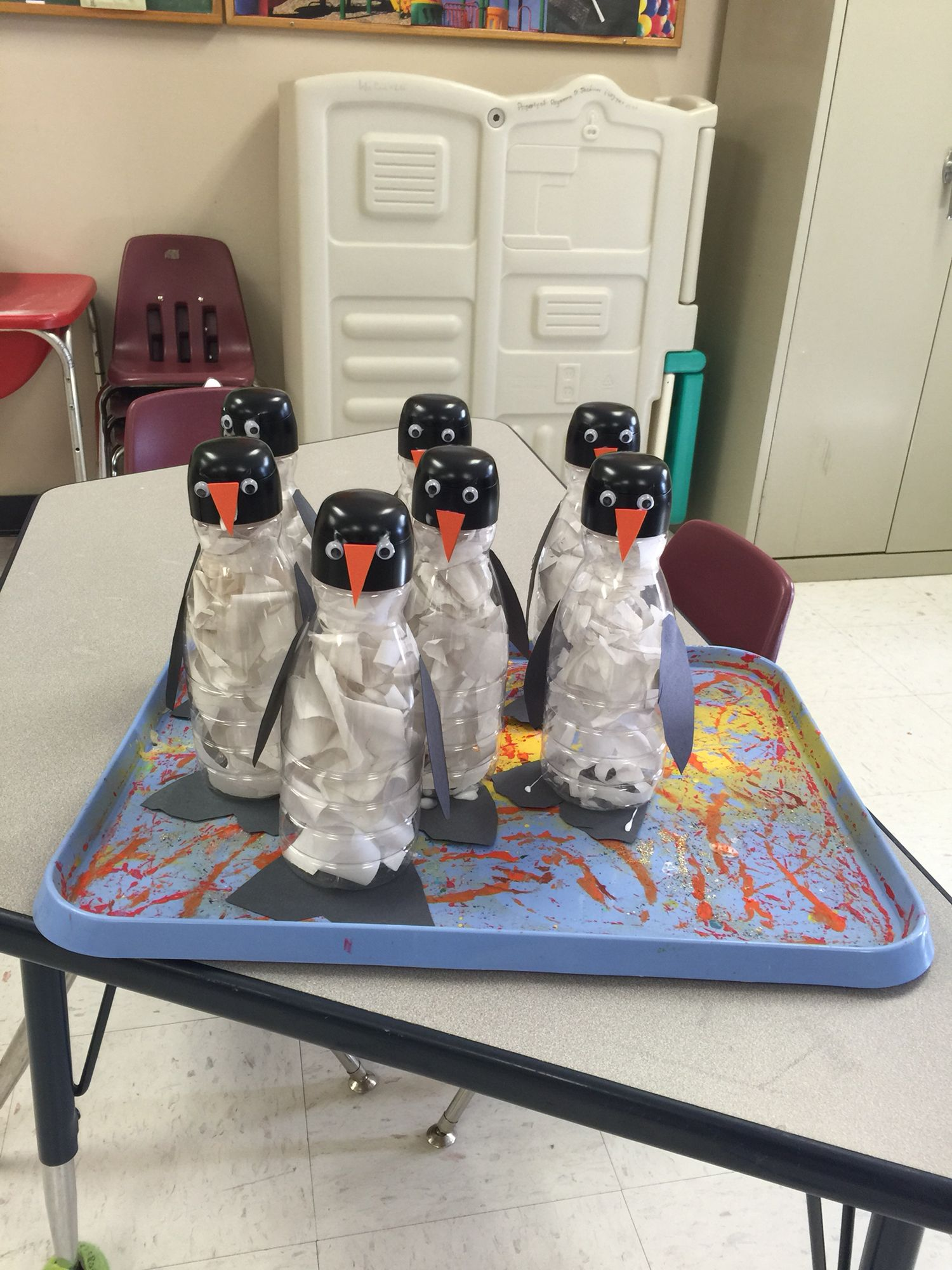 Penguins made from coffee creamer bottles. Used black Krylon Fusion spray paint to paint the tops. Had children rip white construction paper to put inside the bottles.