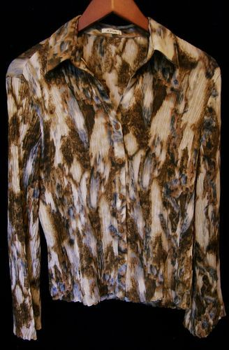 This is a gently worn Jaipur multi color brown tan white long sleeve casual career L Womens Top Blouse. This is a incredibly eye catching garment with an abstract pattern. The fabric has a pleated look with a lot of stretch and could fit an XL person as well. There are 6 brown buttons up the front. The sleeves bell at the end. This top is the epitome of comfort and style. Whoever wears this will receive many compliments.