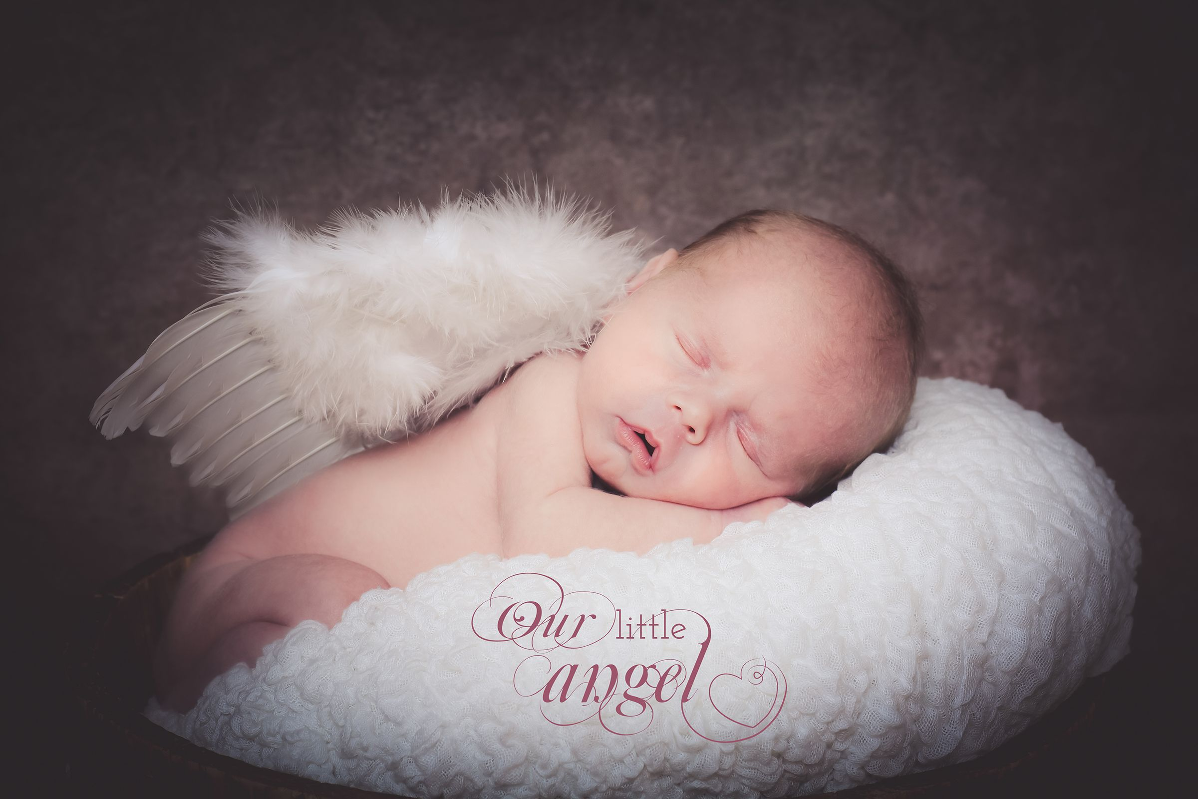 A beautiful baby girls newborn photoshoot using angel wings as a prop