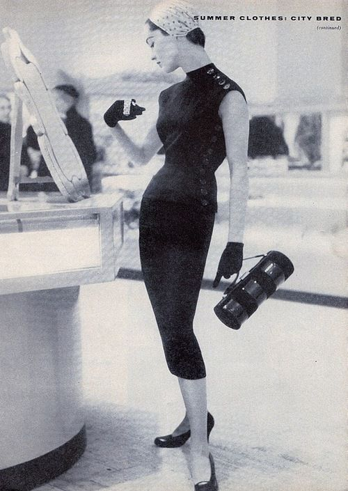 Model in a stylish black summer ensemble with purse, 1950s.