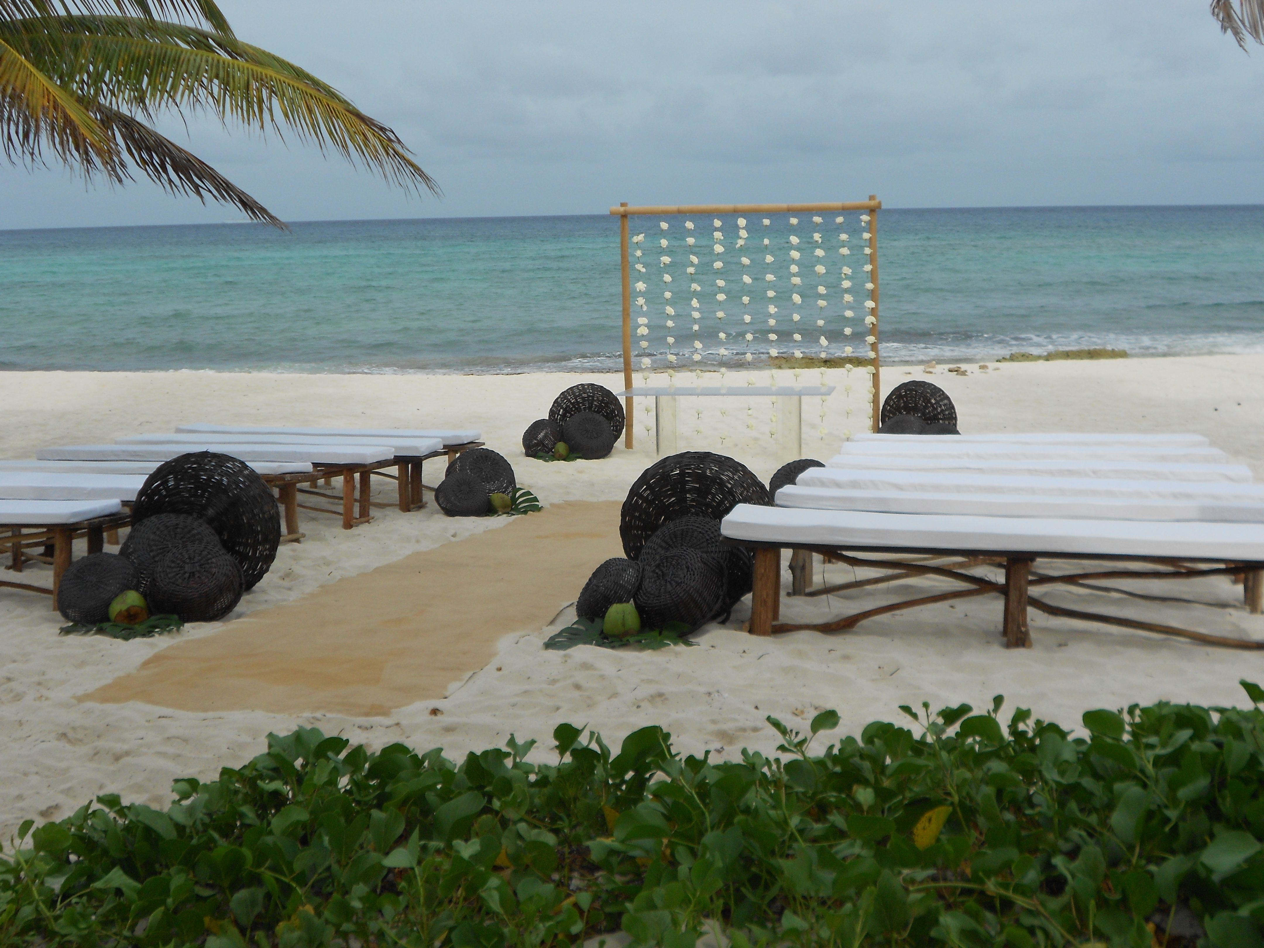 Bali wedding venues on the beach  Beach wedding rattan aisle runner bench seating simple arch
