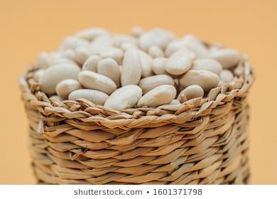 Healthy organic dried white beans in a straw basket