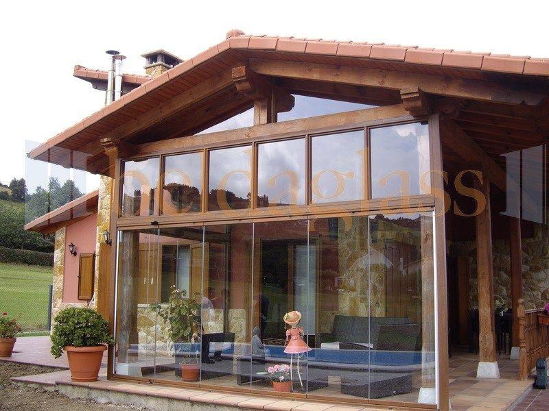 Terraza porche de madera acristalada con cortinas de cristal sin