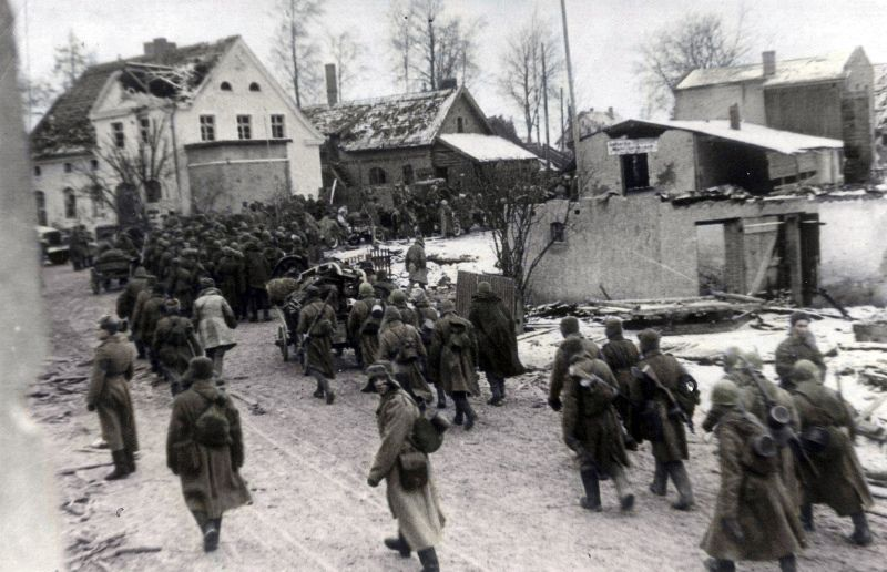 Soviet soldiers moving through a German town on the outskirts of