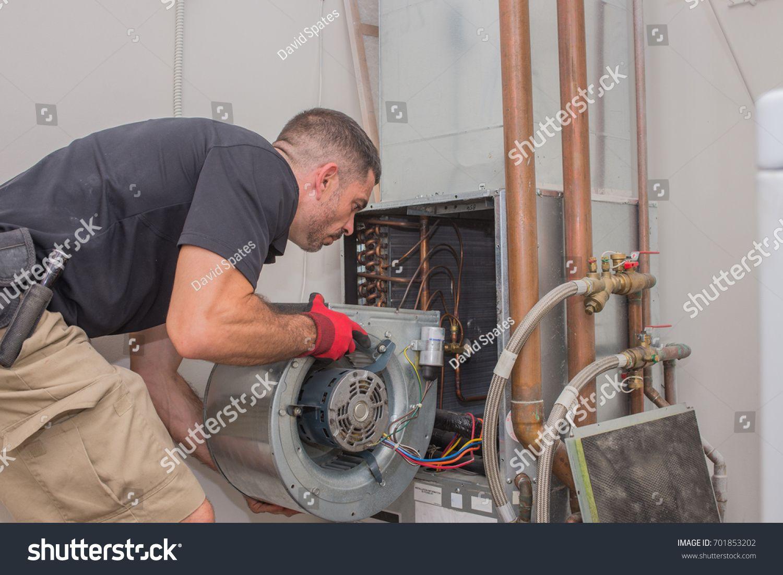 Hvac repair technician removing a blower motor from air