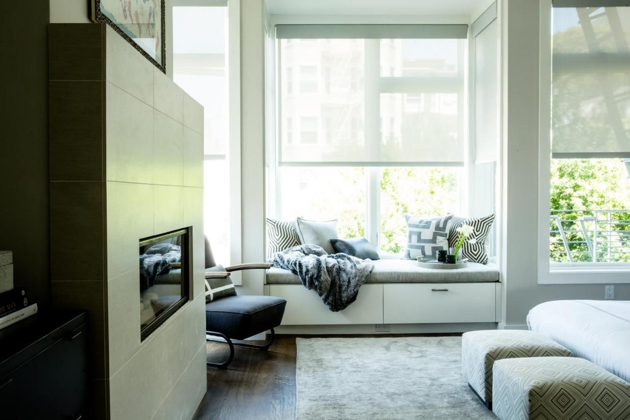 This modern bedroom features a window seat, giving the space a cozy, inviting feel.