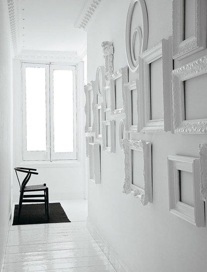 Inspiring black and white decor: Empty white frames on a white gallery wall, whitewashed floors and a stark contrasting black chair and rug.