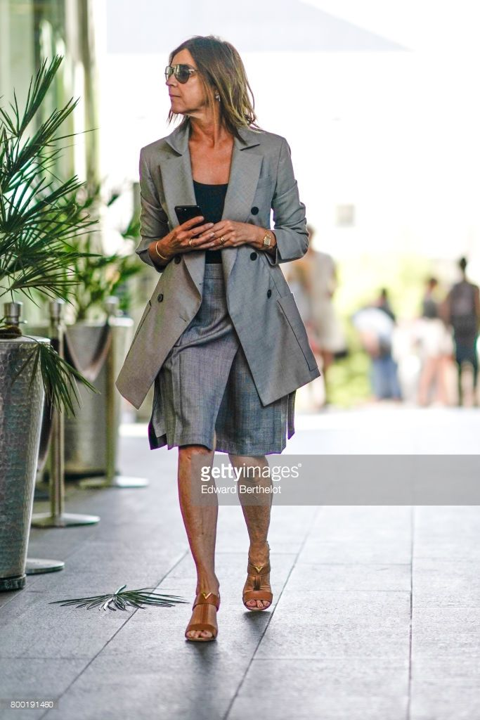 Carine Roitfeld wears sunglasses, a gray blazer jacket, a gray skirt, a black top, and heels, after the CDG Comme des Garcons show, during Paris Fashion Week - Menswear Spring/Summer 2018, on June 23, 2017 in Paris, France.