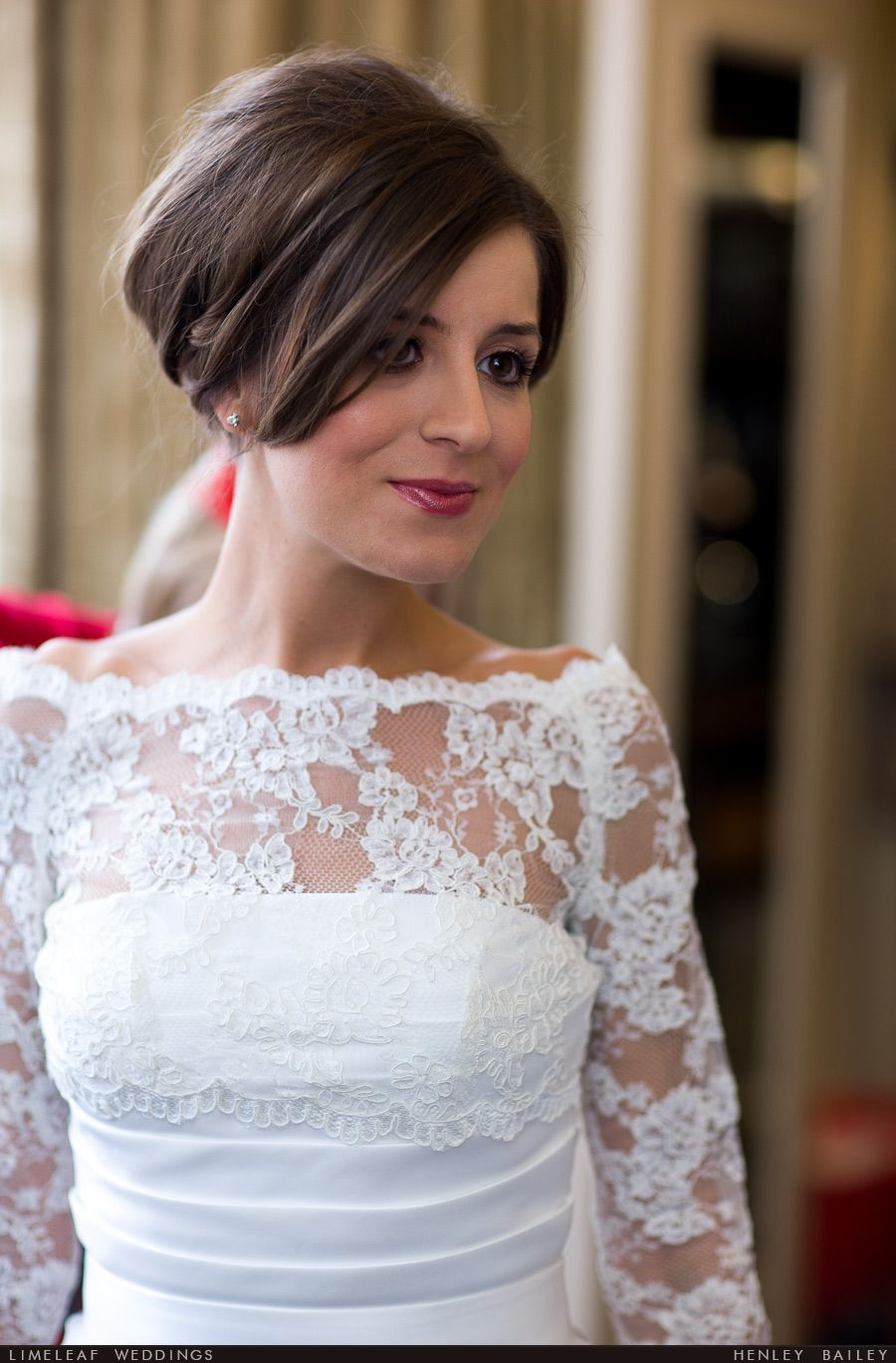 Bride with hair up and white lace shrug over her satin wedding dress ...