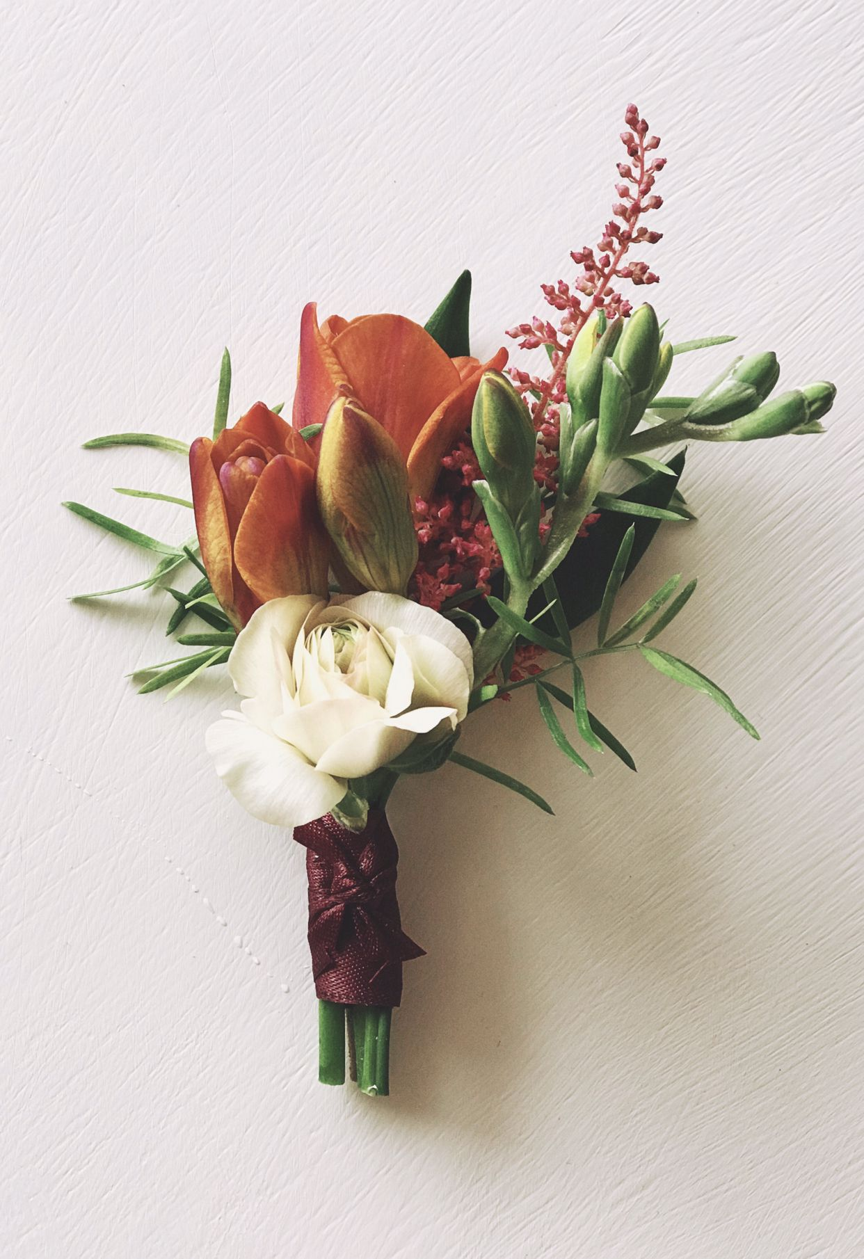 206bca4ae897 Freesia and butterfly ranunculus boutonniere.