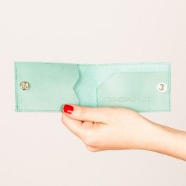 """Das Portemonnaie """"Oli"""" besteht aus Rindsleder und wird durch einen Druckknopf sicher verschlossen. Es hinterlässt kaum Konturen in eurer Skinny Jeans und passt perfekt in jede kleine Handtasche. Im Inneren habt ihr Platz für das Wichtigste: ein paar Geldscheine und zwei Karten. """"Oli"""" ist damit der perfekte Begleiter für euer nächstes Partywochenende.In drei Farben erhältlich: mint, braun, anthrazit/schwarzMaterial: EchtlederMaße: ca. 10 x 6 cmDas Portemonnaie wird von mir in Handarbeit und…"""
