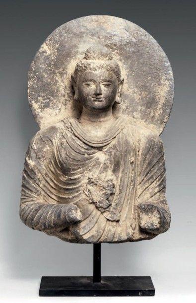 Buste de Bouddha en schiste. Il est vêtu d'une robe monastique plissée, le visage serein, le front rehaussé de l'urna, les cheveux ondulés coiffés en chignon, une auréole derrière la tête. Art Gréco-Bouddhique… - Castor - Hara SVV - 21/03/2016