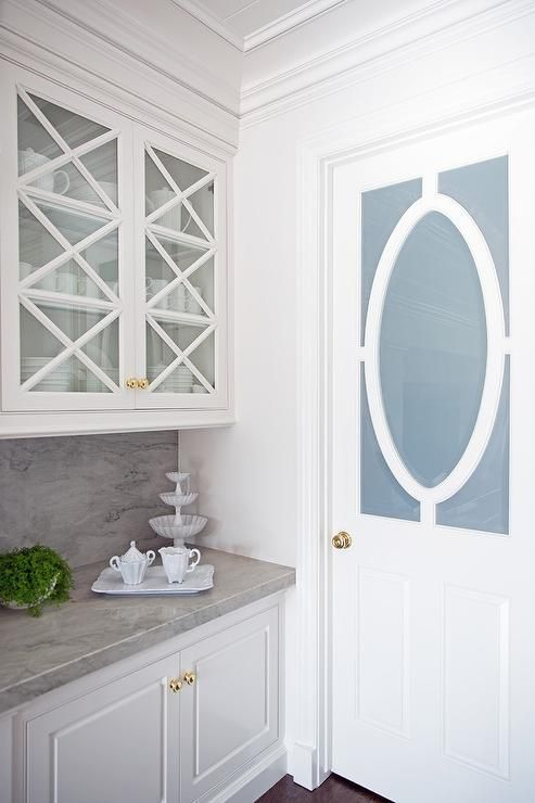 A Frosted Glass Door With Oval Wood Trim Opens To A Kitchen Pantry Filled With Glass Front Up Glass Pantry Door Frosted Glass Pantry Door Kitchen Pantry Design